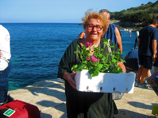 Una-signora-arrives-with-geraniums-for-her-Giannutri-garden