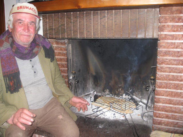 Peppe-toasts-bread-for-bruschetta-in-the-fireplace