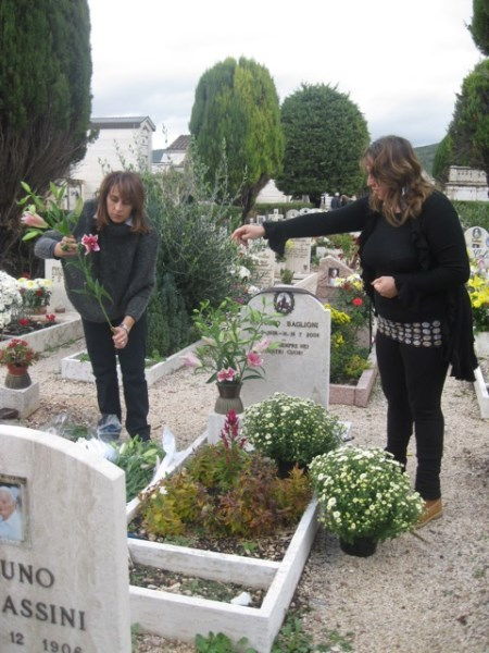 Two sisters lovingly arrange flowers for their beloved Papà