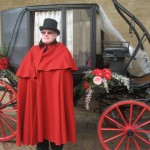 In scarlet cape, past Priore Servente before postal stagecoach