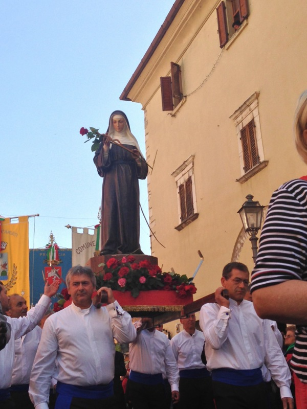 Santa Rita is born on the shoulders of proud men as the faithful give her roses