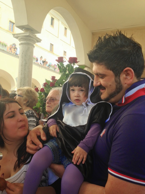 Vincenzo brings his little Elisabetta Rita - dressed like Santa Rita! - to Cascia for the celebrations