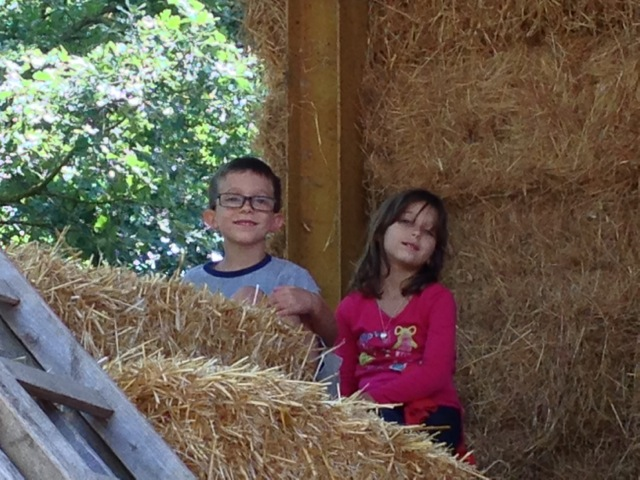 Luke and Maggie climb the hay  bales
