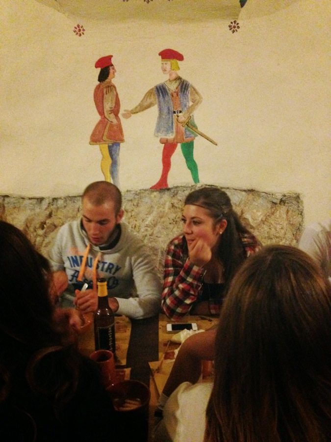 A young couple feasts under a medieval couple courting