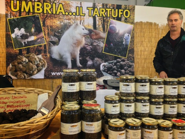 This truffle vendor stands proudly in front of the poster - starring HIS dog!