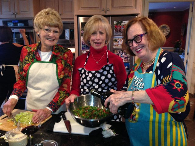 Paula adds the olive oil with Debbie and Betty approving