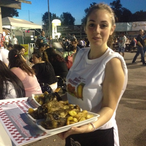 Young volunteer, Martina, serves up the roasted pork shank with roasted potatoes