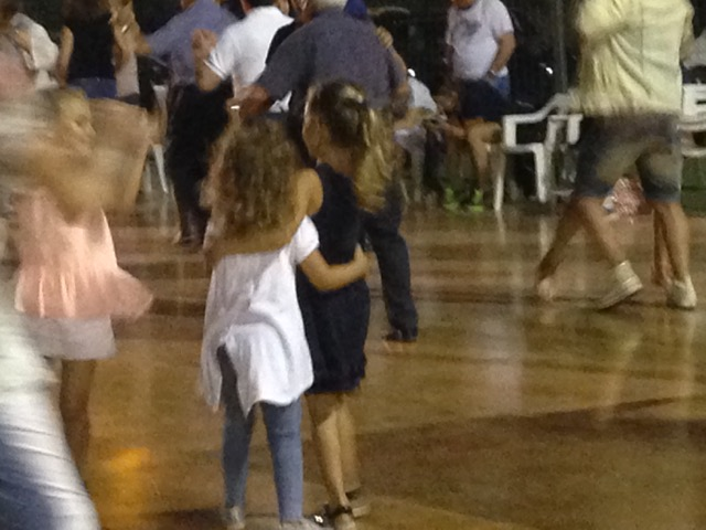 Little ones learn to dance by following the adults on the dance floor
