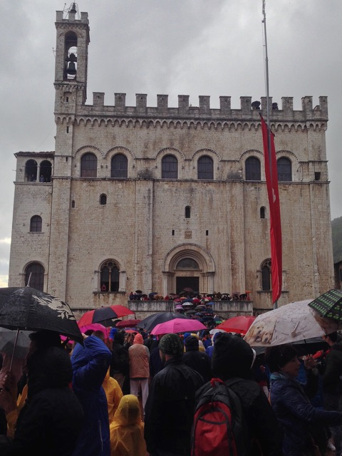Umbrellas are up in Palazzo dei Consoli as all await the arrival of the Ceri - but spirits are not damp