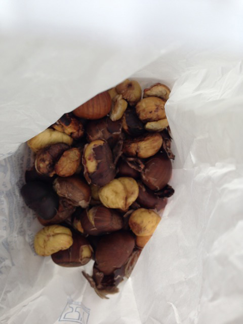 A white paper bag of roasted chestnuts to much as you stroll along