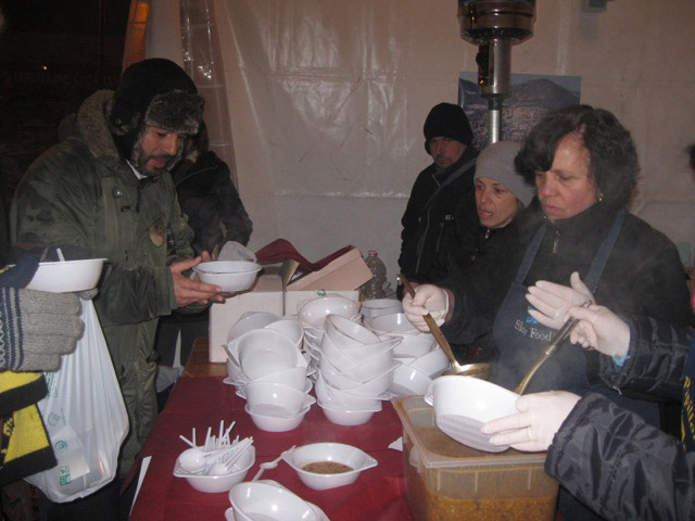 Silvana and other volunteers serve up steamy bowls of roveja soup
