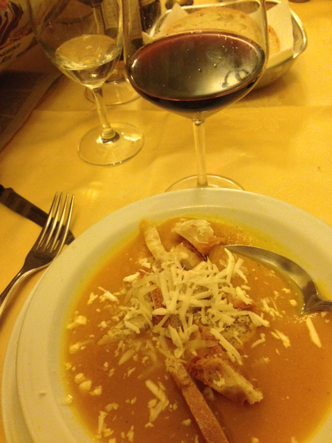A creamy squash soup with toasted bread, Parmesan shavings