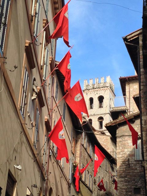 Red flags flutter over Lower Assisi la Parte de Sotto streets
