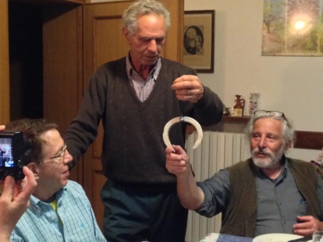 Marino proudly shows a wild boar tusk to Roger and to Pino