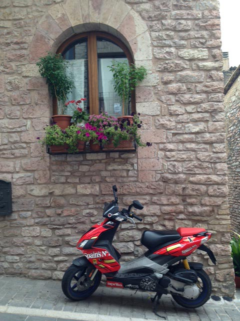 A-Vespa-red-blends-with-floral-colors-on-an-Assisi-street